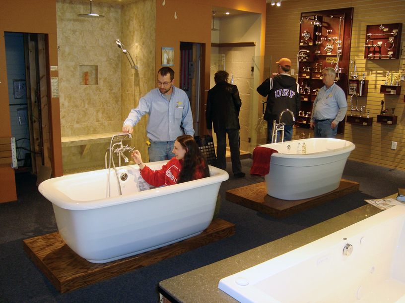 Showroom customer being helped by employee testing out soaker bathtub