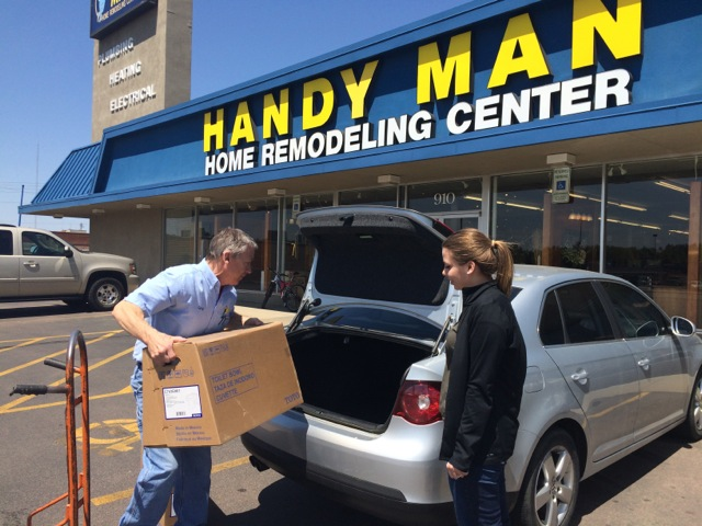 Employee helping young woman load box into car