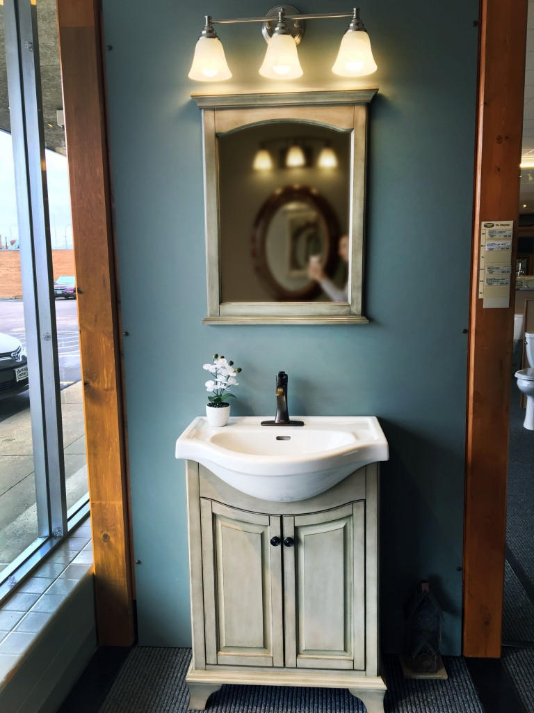 Small potbelly vanity vignette with mirror and light bar