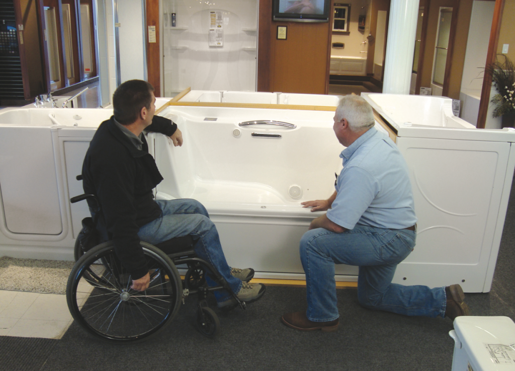 man in wheelchair looking at walk in tub